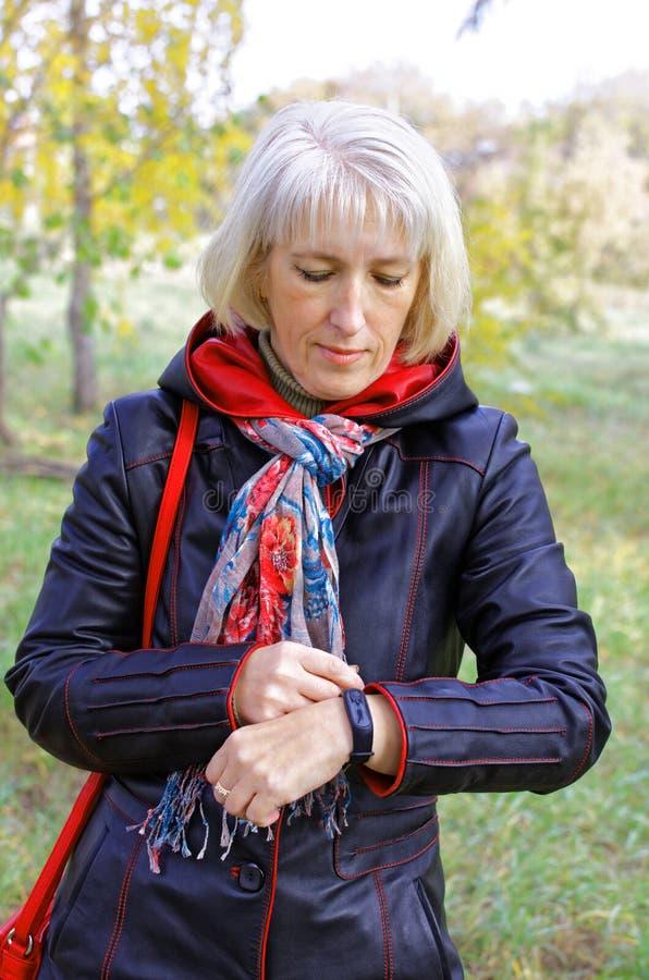 Uma mulher usa um bracelete da aptidão ao andar no parque fotos de stock royalty free
