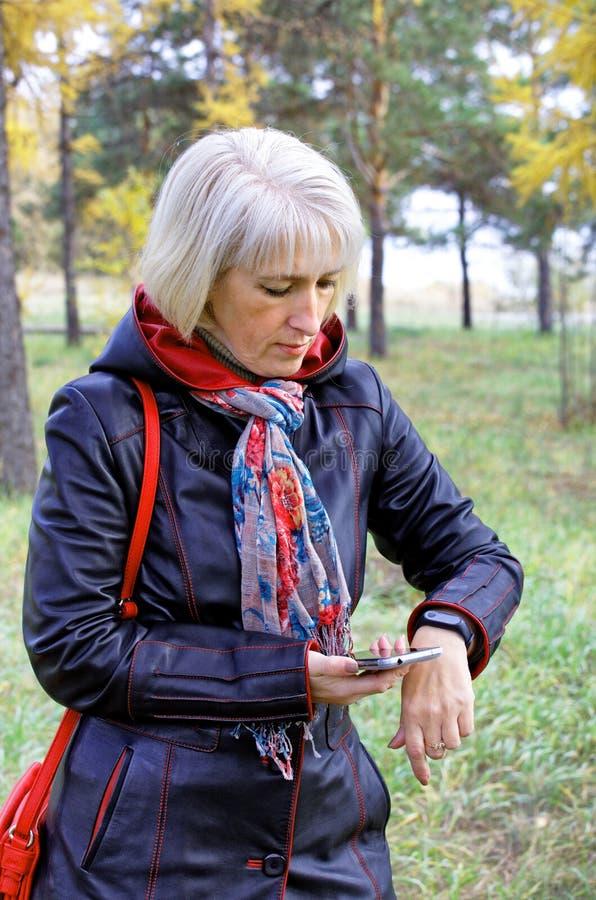 Uma mulher usa um bracelete da aptidão para ler seus dados da saúde foto de stock
