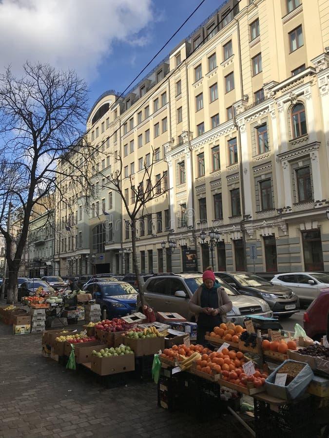 Uma mulher vende o fruto fora das portas douradas em Kyiv - UCRÂNIA imagem de stock royalty free