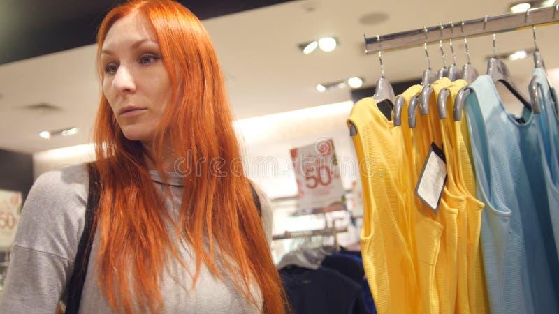 Uma mulher vermelha do cabelo que anda entre vestidos na loja da roupa foto de stock