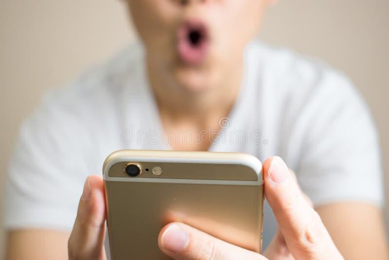 Uma mulher veste os t-shirt brancos chocados muito Após ter recebido uma mensagem do telefone fotografia de stock royalty free