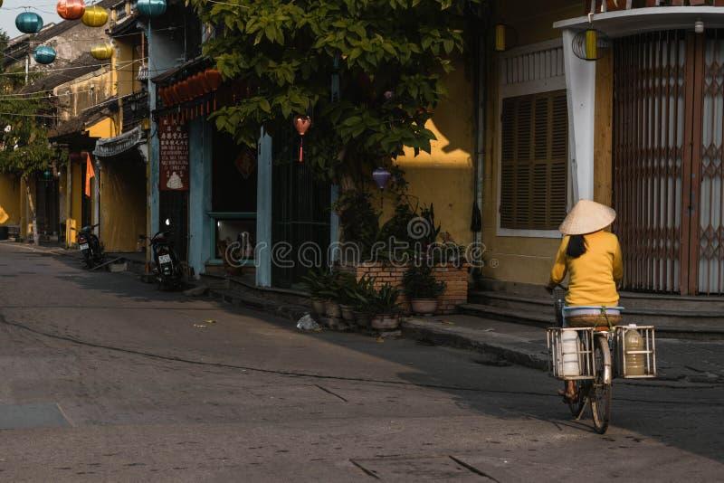 Uma mulher vietnamiana local monta sua bicicleta para trabalhar no hoi imagens de stock