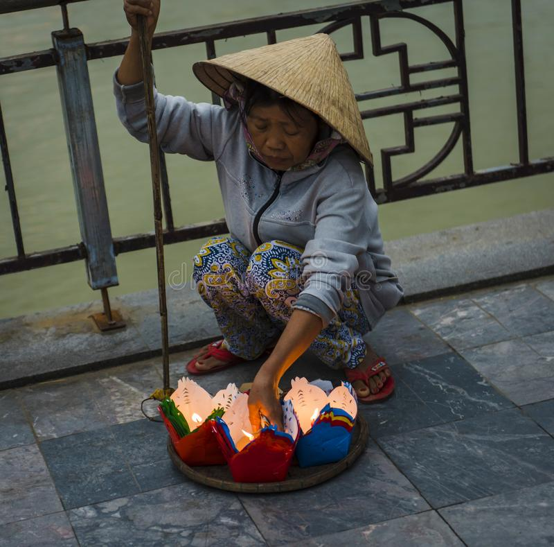 Uma mulher vietnamiana, vendendo velas da lanterna, para o festival de lanterna da Lua cheia, na cidade antiga imagem de stock