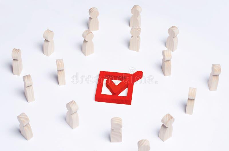 Uma multidão de povos olha o tiquetaque vermelho grande na caixa O concentrado imagem de stock