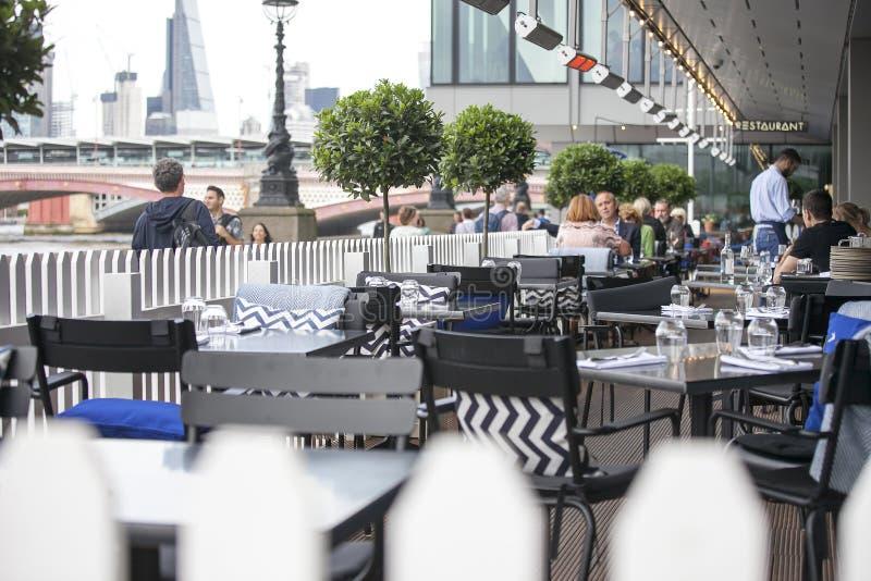 Uma multidão heterogêneo senta-se fora do bar, bebe a cerveja, fala com amigos Southbank imagem de stock royalty free