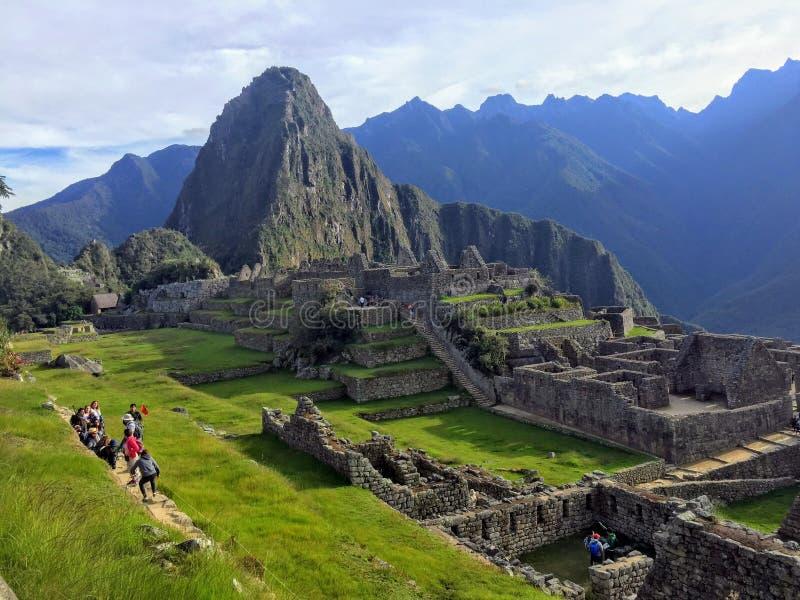 Uma multidão pequena de turistas admira as vistas incríveis de Machu Picchu no Peru imagens de stock royalty free