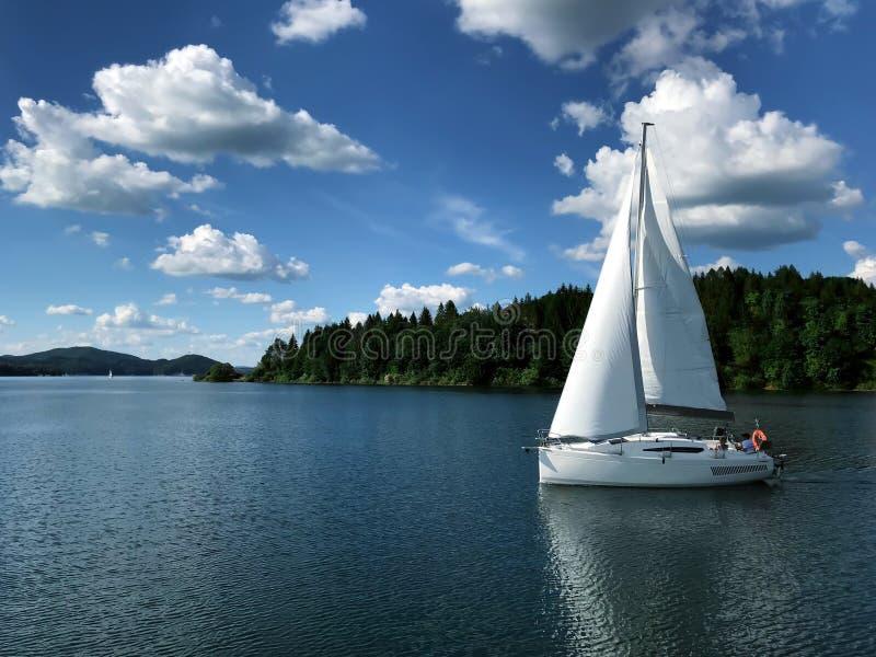 Uma navigação do veleiro em um rio/lago Atividades ao ar livre Na perspectiva da floresta, das montanhas e do céu azul bonito com imagens de stock