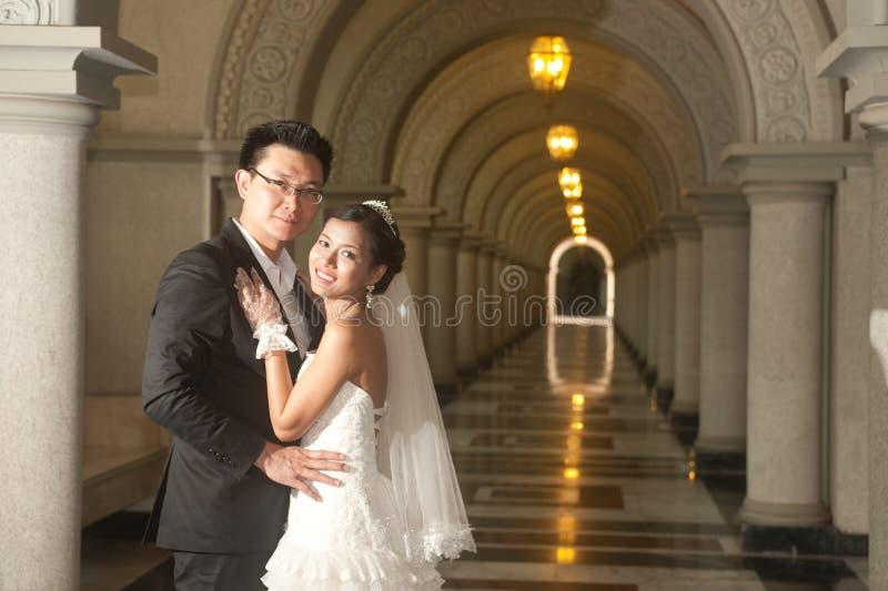 Uma noiva bonita e um noivo considerável na igreja cristã durante o casamento. imagem de stock
