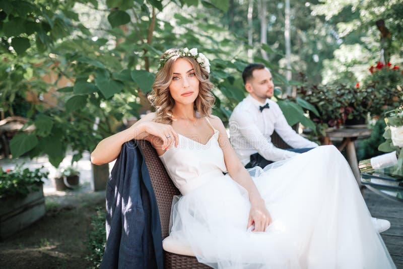Uma noiva bonita em um vestido e em uma grinalda brancos de casamento senta-se em uma cadeira ao lado do noivo, descansando imagens de stock