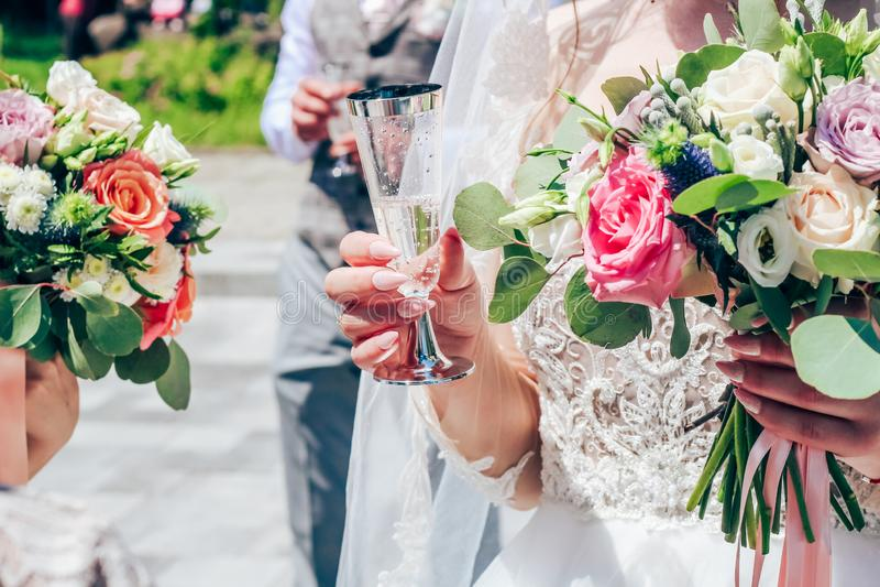 Uma noiva com os pregos nude longos está guardando um vidro do champanhe Close-up imagens de stock