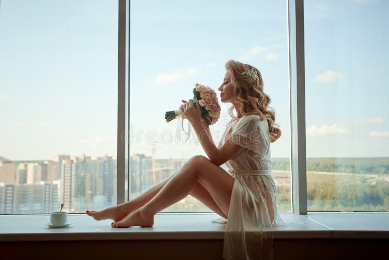 Uma noiva da moça no peignoir que senta-se na soleira com um ramalhete Preparação da manhã do casamento fotos de stock