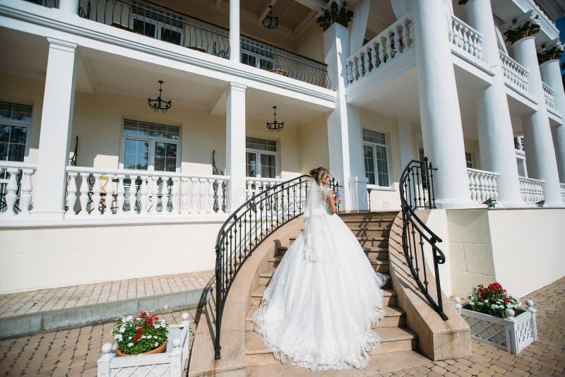 Uma noiva delgada em um vestido de casamento com um trem longo vai acima das etapas ao palácio A menina está guardando um bonito imagens de stock royalty free
