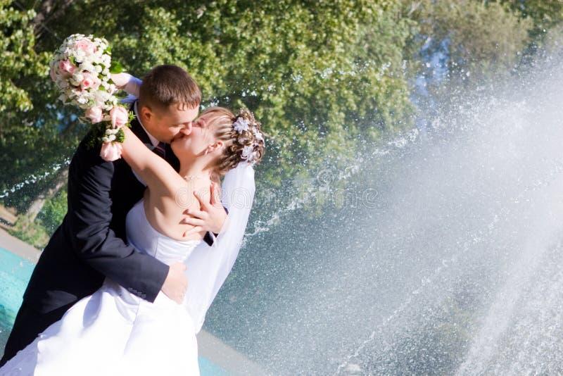 Uma noiva e um noivo que beijam perto da fonte foto de stock