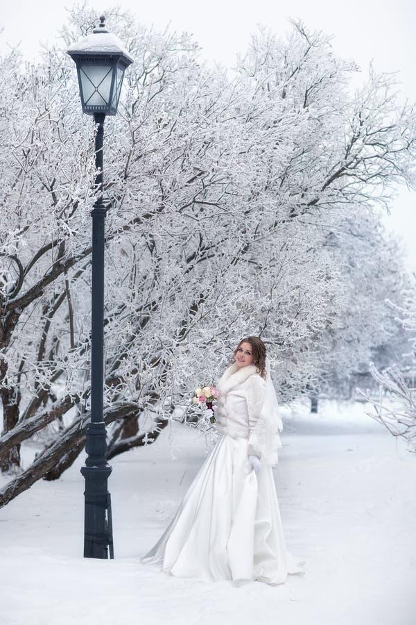 Uma noiva em um casaco de pele branco em uma rua gelado ao lado de uma lanterna fotos de stock