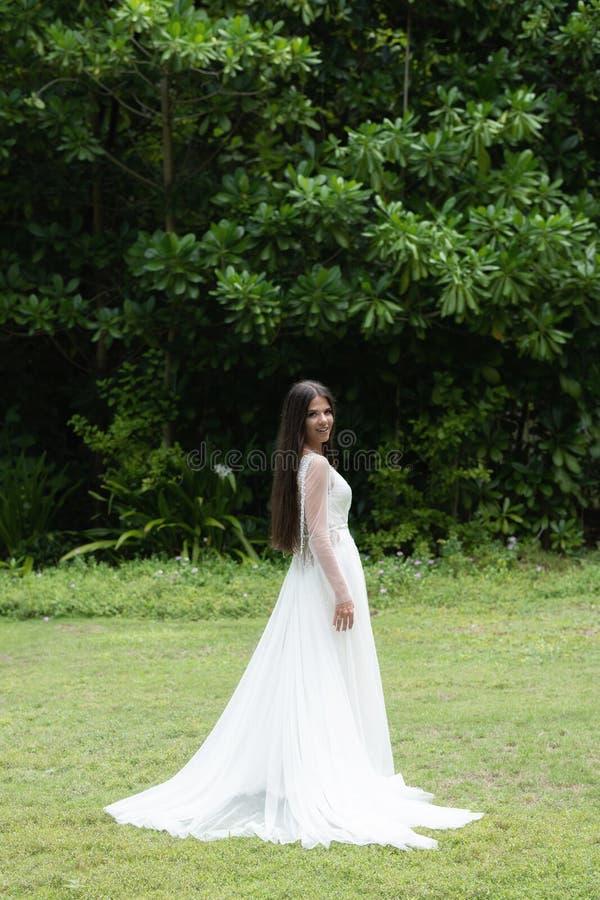 Uma noiva em um vestido branco está estando em um gramado verde No fundo é uma floresta tropical imagem de stock royalty free