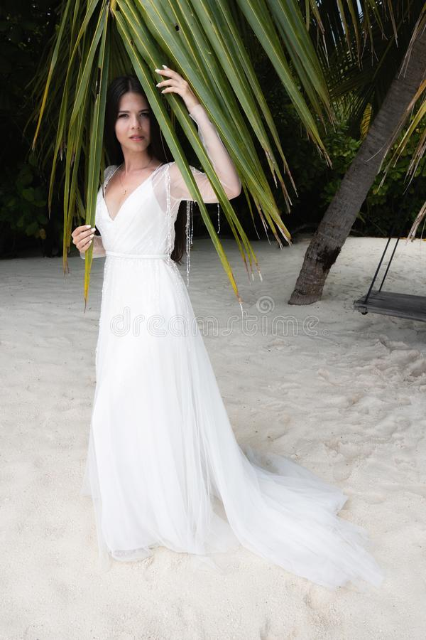 Uma noiva em um vestido branco está estando sob uma folha enorme da palma foto de stock royalty free