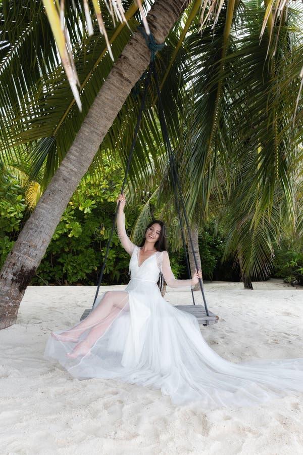 Uma noiva em um vestido branco está montando em um balanço sob uma palmeira grande foto de stock