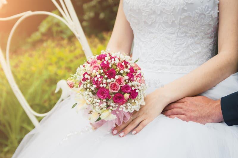 Uma noiva em um vestido de casamento branco está guardando um ramalhete em suas mãos Close-up, foco seletivo fotografia de stock royalty free