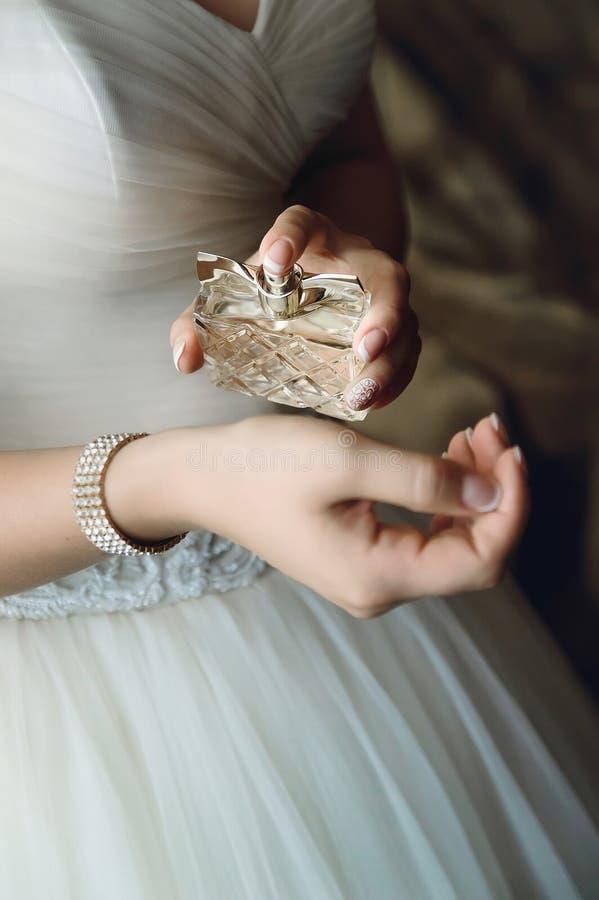 Uma noiva em um vestido de casamento branco polvilha o perfume em seu pulso imagem de stock royalty free