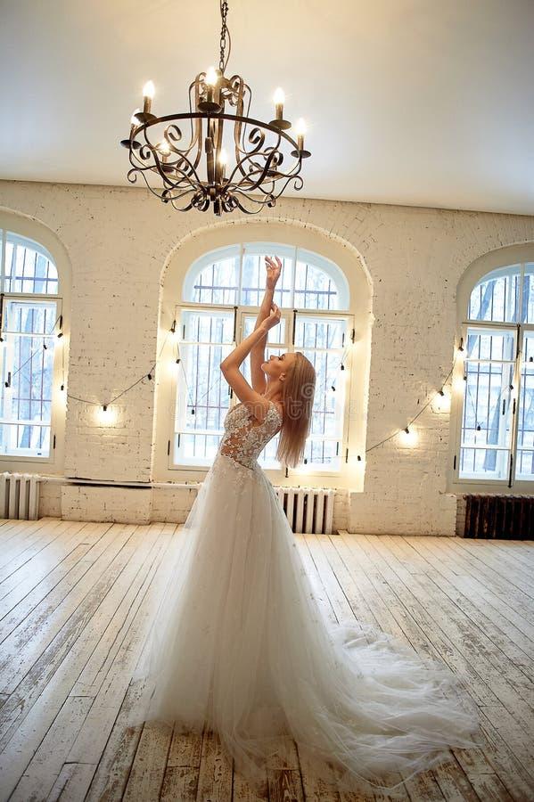 Uma noiva graciosa em um vestido do la?o puxa para cima suas m?os Sala no estilo do s?t?o fotografia de stock royalty free