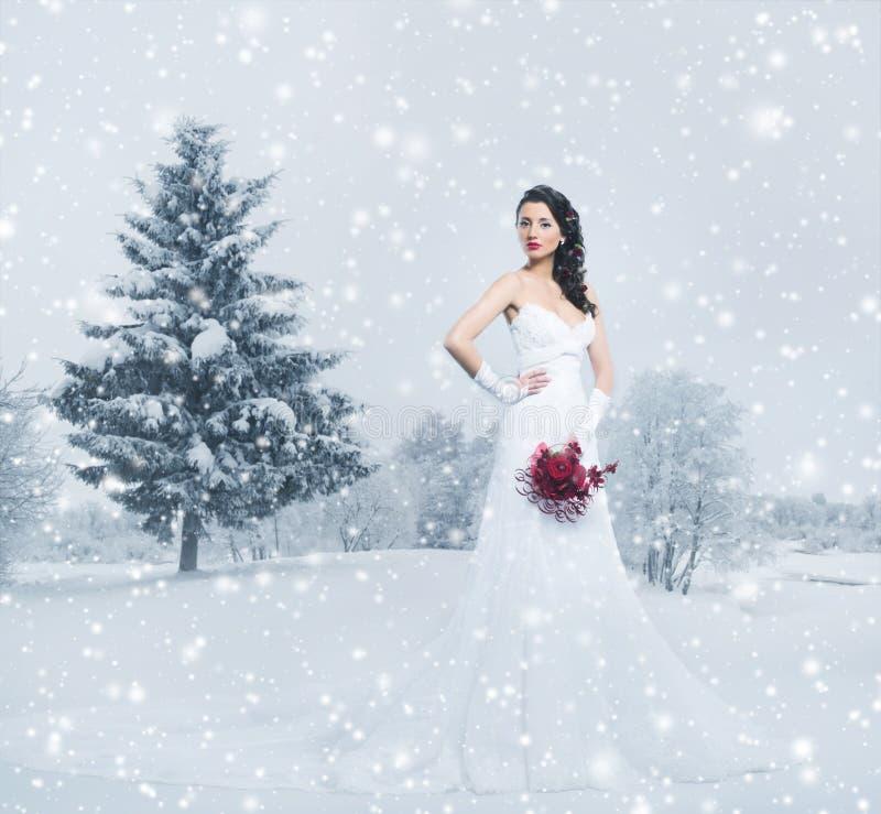 Uma noiva moreno nova em um vestido branco na neve imagens de stock royalty free