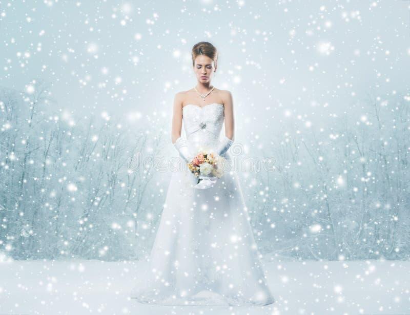 Uma noiva nova do ruivo em um vestido branco na neve imagens de stock royalty free