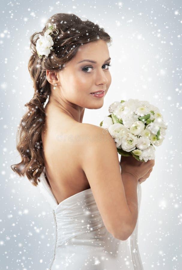 Uma noiva nova em uma terra arrendada branca do vestido floresce imagens de stock royalty free