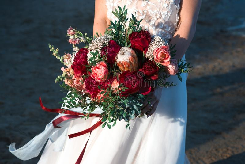 Uma noiva que guarda o ramalhete do casamento em suas mãos fotos de stock royalty free