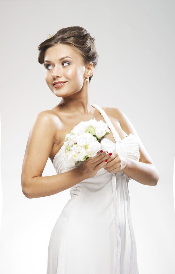 Uma noiva triguenha nova que prende um ramalhete da flor fotos de stock royalty free