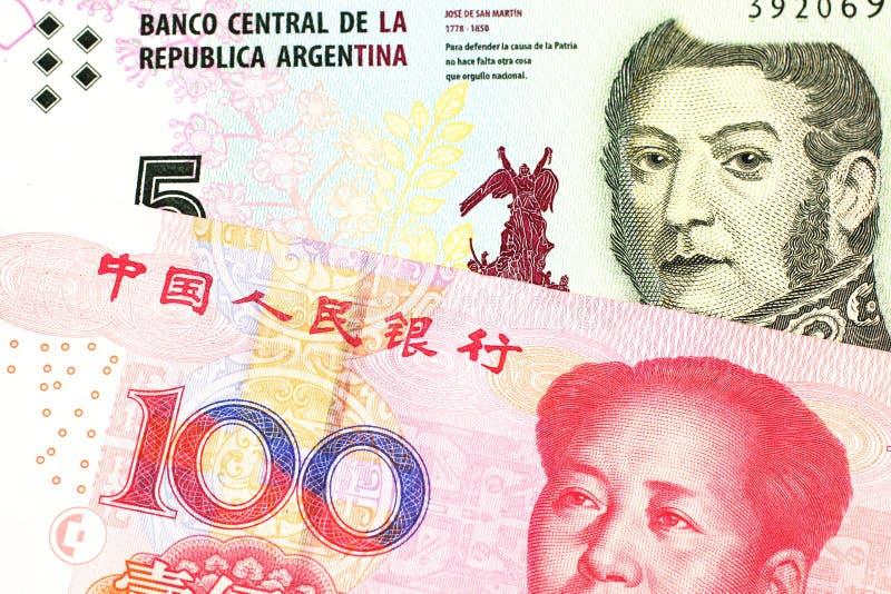 Uma nota de Argentina, fim do peso acima com um chinês, conta do yuan imagem de stock royalty free