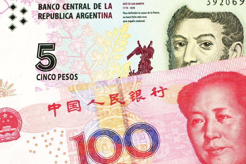 Uma nota de Argentina, fim do peso acima com um chinês, conta do yuan foto de stock royalty free