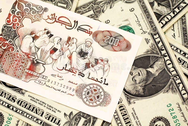 Uma nota do dinar de argelino com notas de dólar do americano um fotos de stock royalty free