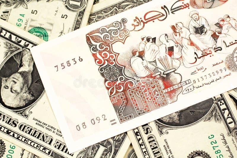 Uma nota do dinar de argelino com notas de dólar do americano um imagem de stock