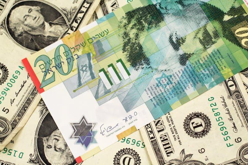 Uma nota do shekel vinte de Israel em uma cama das notas de dólar uma imagem de stock