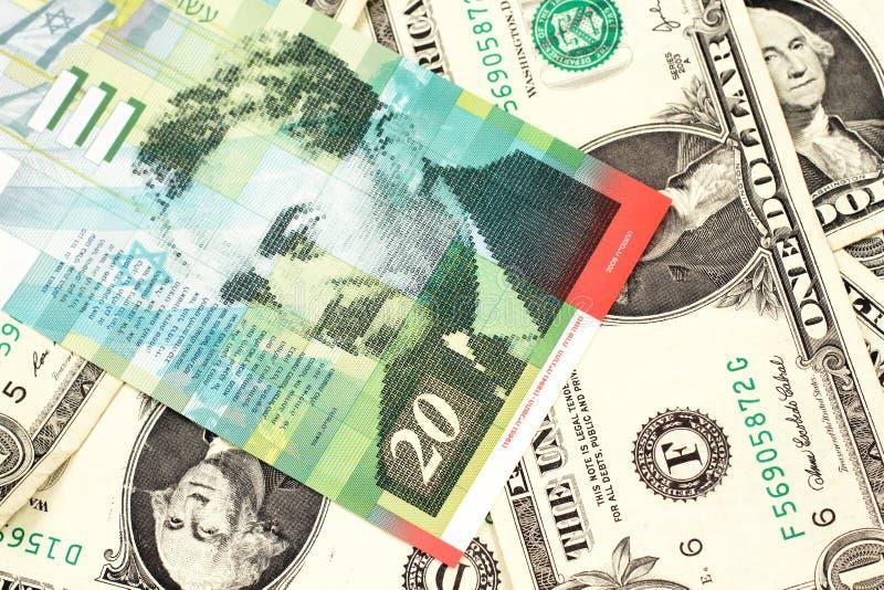 Uma nota do shekel vinte de Israel em uma cama das notas de dólar uma fotos de stock royalty free