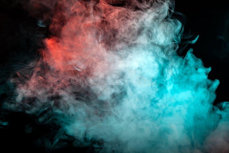Uma nuvem branca da dispersão do fumo denso, iluminada por cores diferentes e expirada de um cigarro, rola acima nas ondas, aumen fotos de stock royalty free