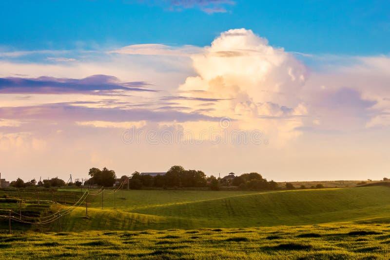 Uma nuvem encaracolado pitoresca sobre o prado durante o nascer do sol ou fotografia de stock royalty free