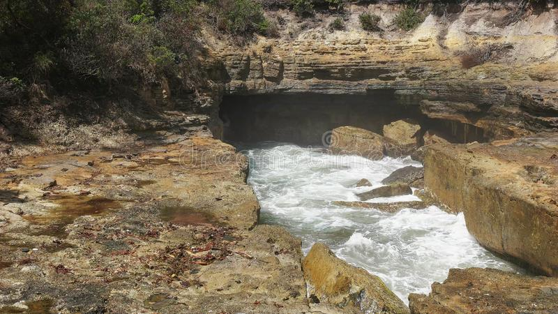 Uma onda deixa de funcionar no furo do sopro no pescoço do eaglehawk, Tasmânia imagem de stock