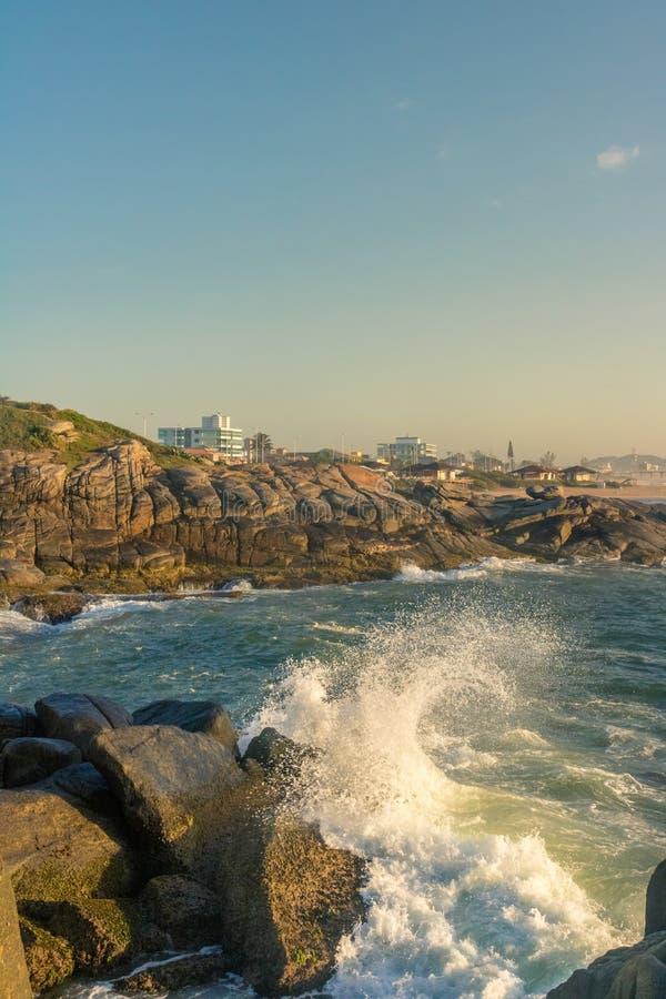 Uma onda deixa de funcionar nos rockes na praia no amanhecer imagens de stock