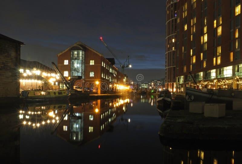 Uma opinião da noite do canal de leeds com a entrada ao cais do celeiro e aos desenvolvimentos modernos da margem e a luz refleti foto de stock