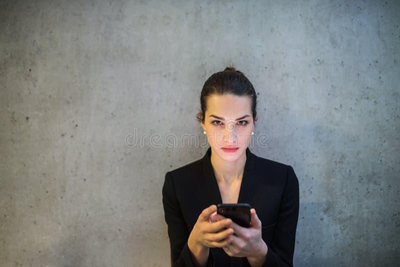 Uma opinião dianteira a mulher de negócio nova com posição do smartphone contra o muro de cimento no escritório imagens de stock