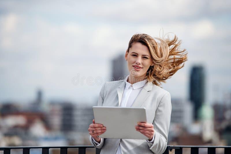 Uma opinião dianteira a mulher de negócios nova com a tabuleta que está em um terraço fotos de stock royalty free