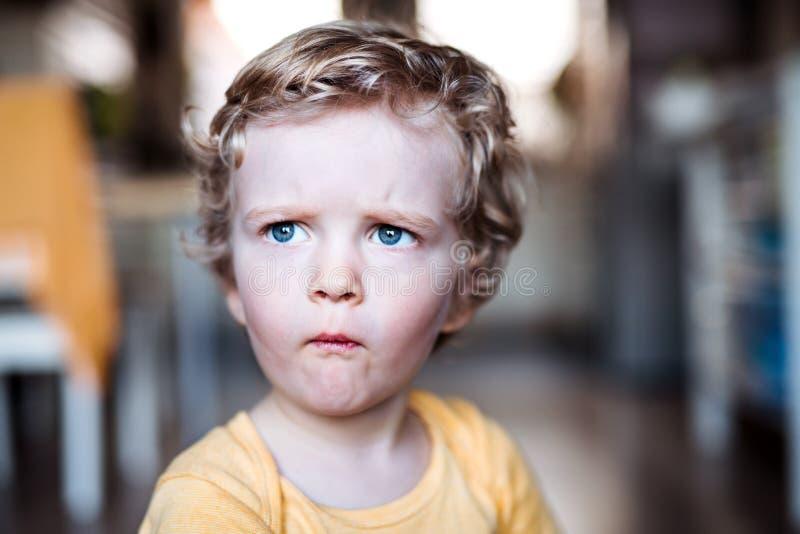 Uma opinião dianteira um menino da criança em casa imagens de stock
