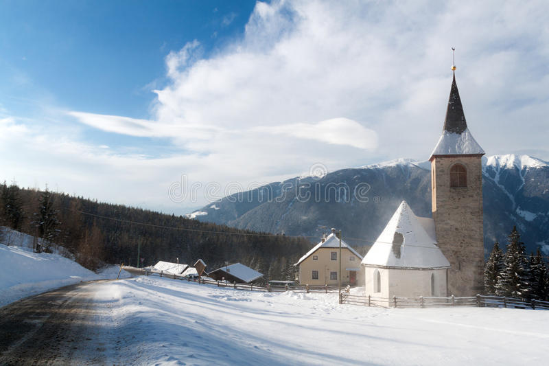 Uma opinião do inverno de uma igreja pequena com um steeple alto imagens de stock royalty free