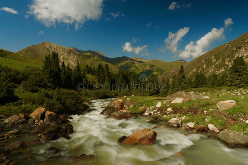Uma opinião do vale de um rio que corre através das montanhas, Quirguizistão imagem de stock