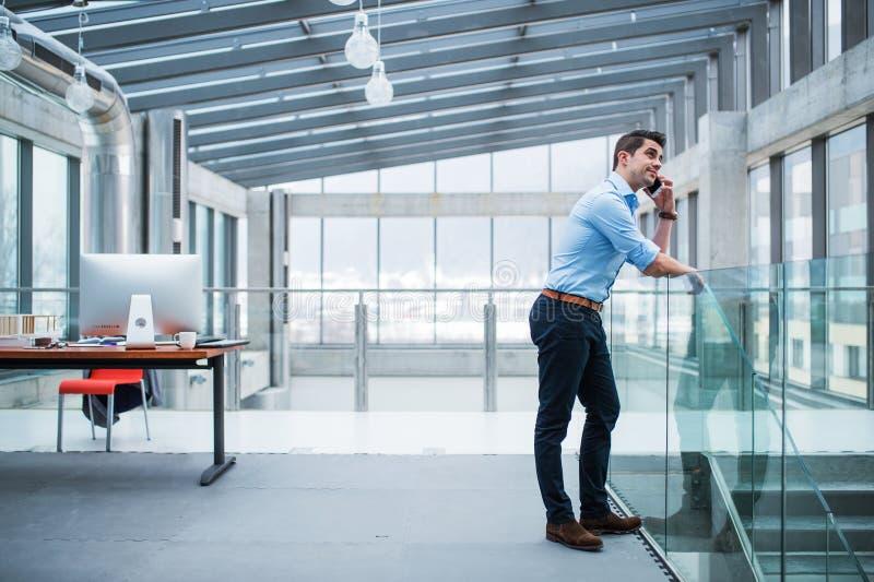 Uma opinião lateral o homem de negócios novo com smartphone em um escritório imagens de stock