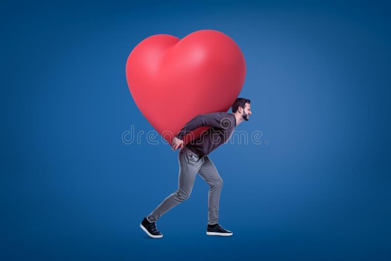 Uma opinião lateral um homem considerável novo em um equipamento ocasional que leva um coração vermelho enorme no seu para trás imagem de stock