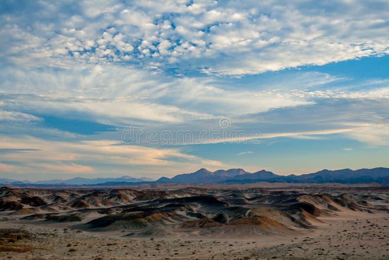 Uma opinião mágica do início da noite das nuvens, do deserto e das montanhas distantes em Egito foto de stock