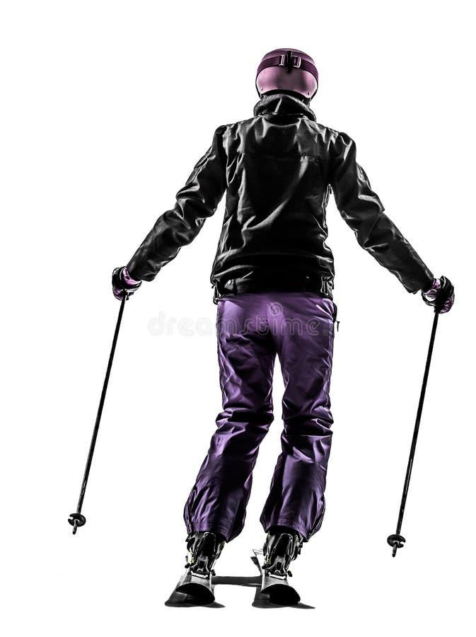 Uma opinião traseira da silhueta do esqui do esquiador da mulher imagem de stock royalty free