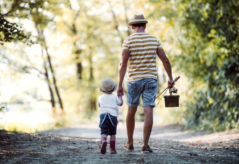 Uma opinião traseira o pai com uma pesca indo do filho pequeno da criança imagens de stock